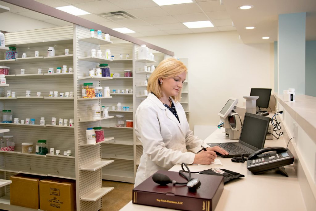 Leah B. Argie working at the pharmacy behind the counter
